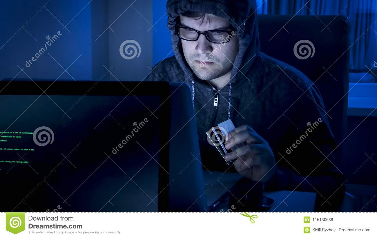 Closeup portrait of young hacker in hood stealing money from bank credit cards