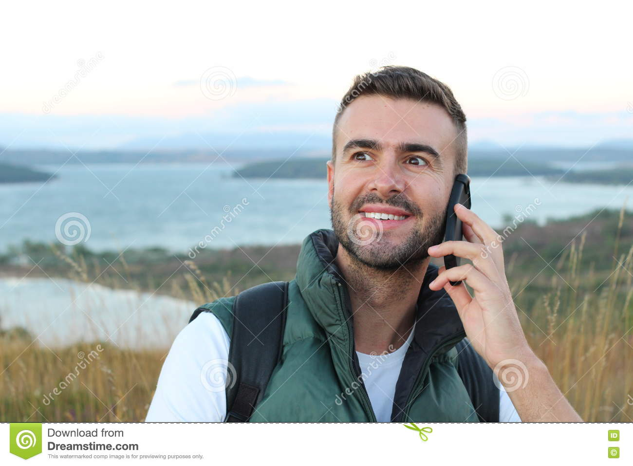 Closeup portrait, young happy ecstatic man with hand on wide open eyes and mouth talking on cell phone, isolated outdoors outside
