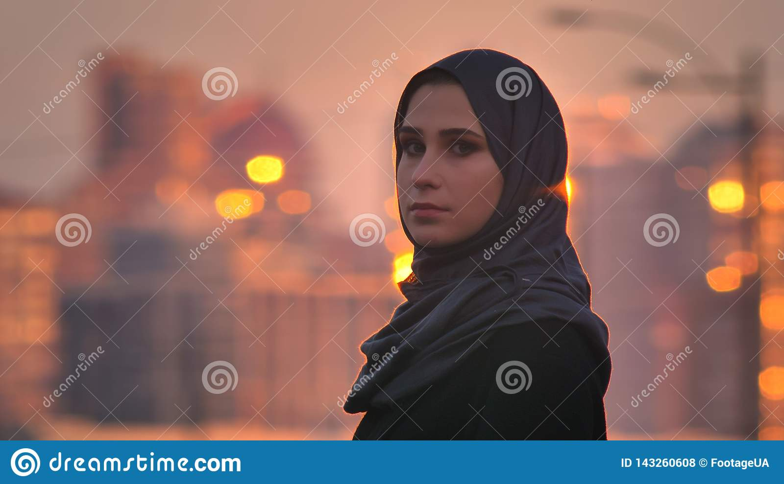 Closeup portrait of young pretty female in hijab turning and looking at camera with shining buildings on the background