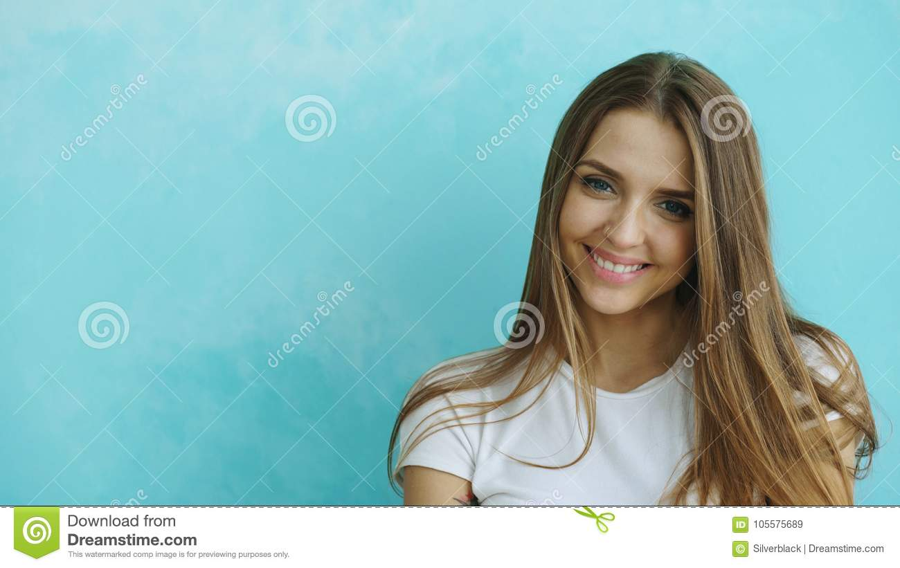 Closeup portrait of young smiling and laughing woman looking into camera on blue background
