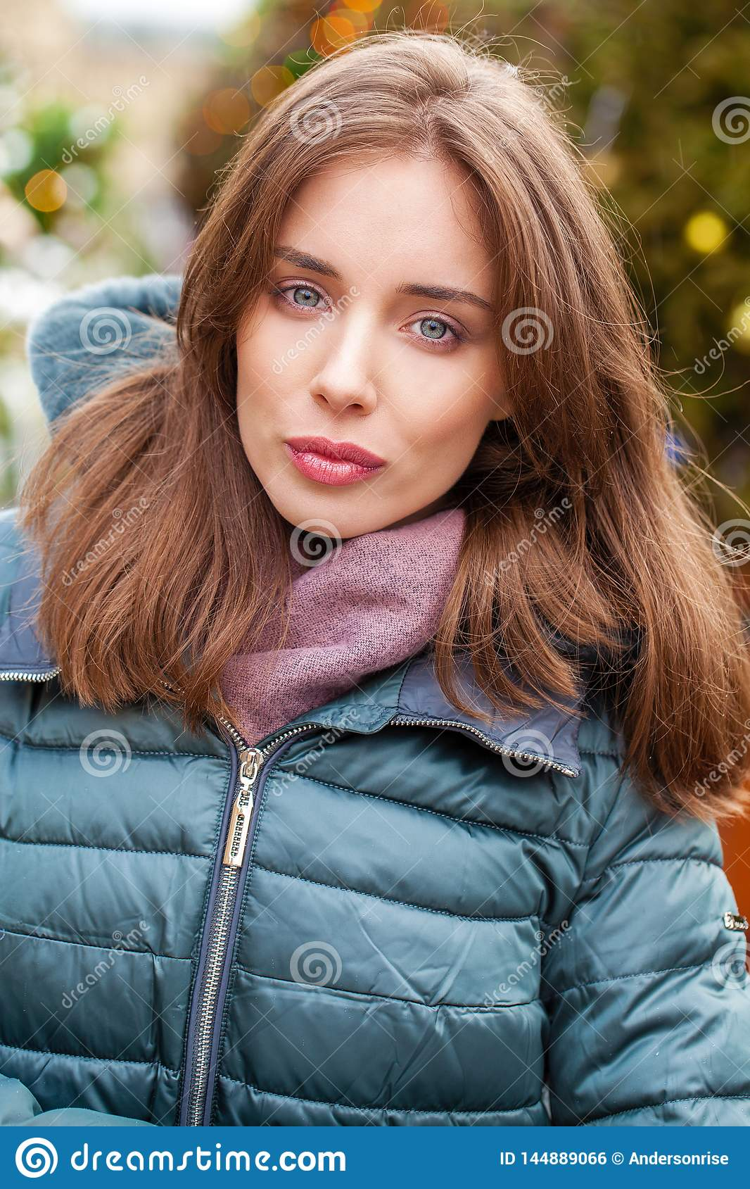 Closeup portrait of a young woman in the winter down jacket