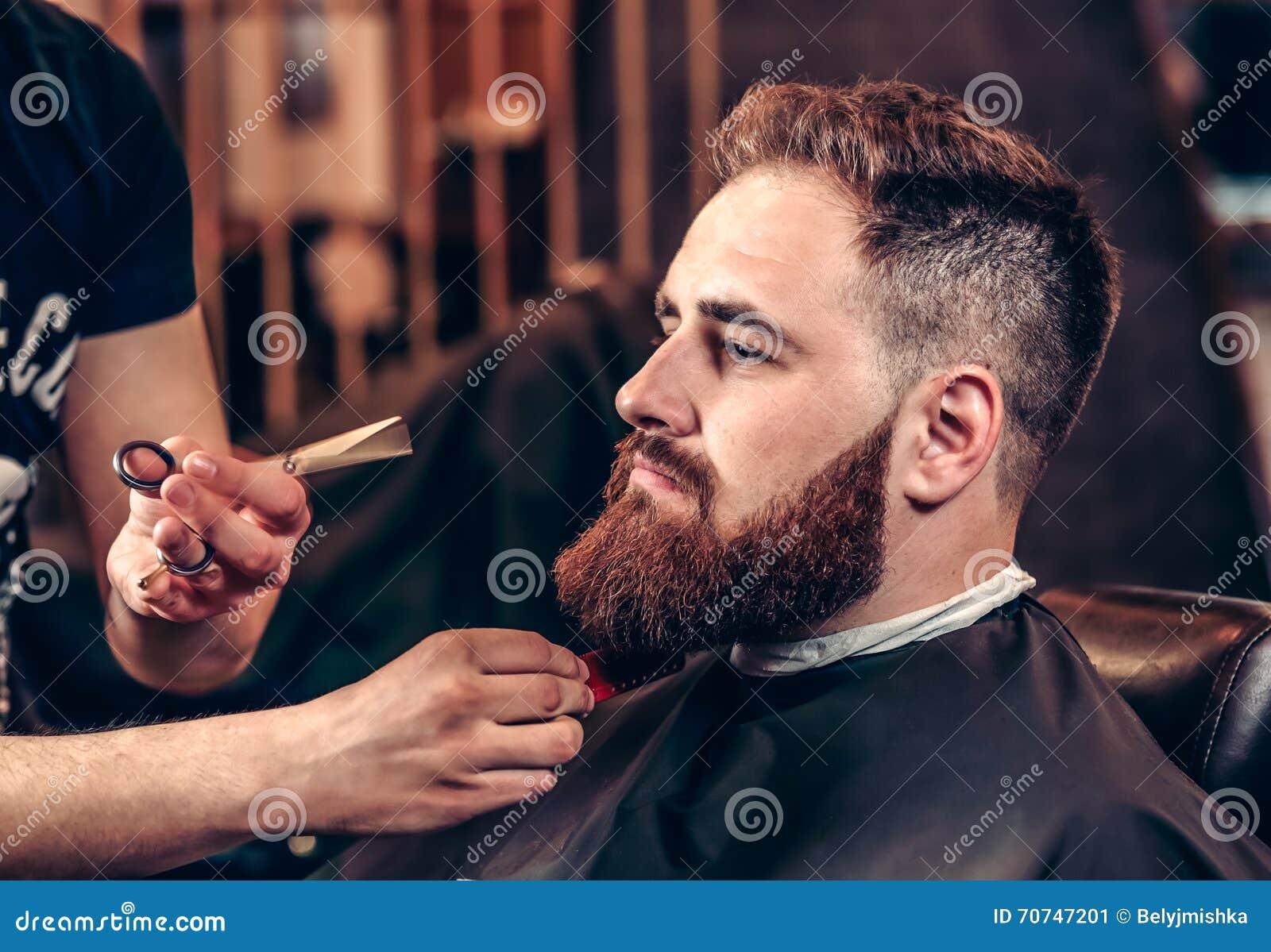 Closeup professional grooming beard with scissors
