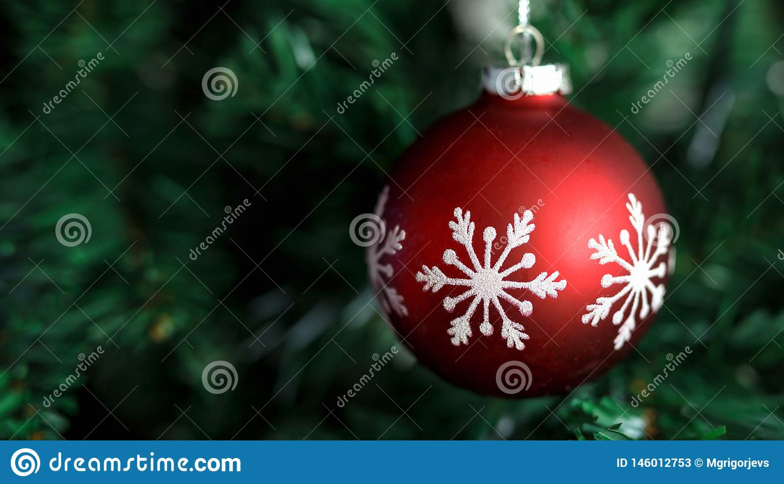 Closeup of red bauble hanging on decorated Christmas and New Year tree