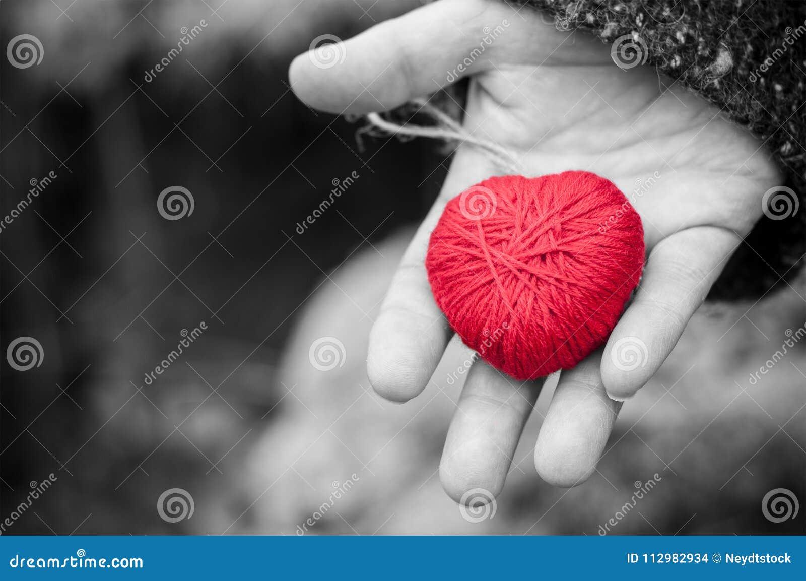 red woolen heart in hand of woman in outdoor
