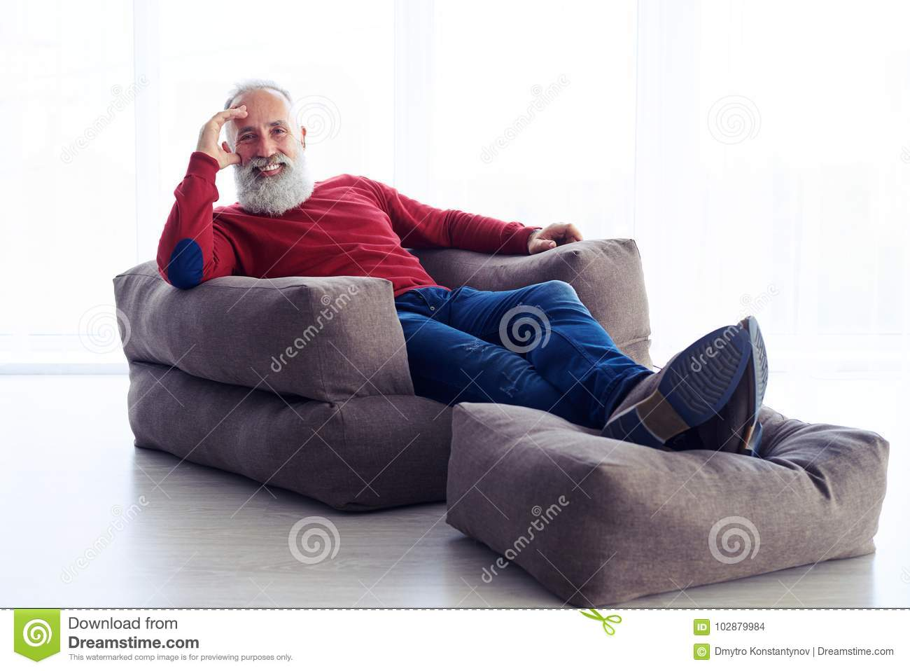 Relaxed bearded man sitting in armchair next to the window at ho