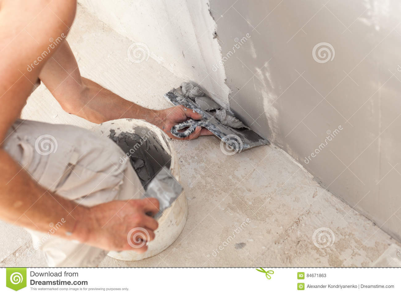 Closeup of repairman hand plastering a wall with putty knife or spatula.