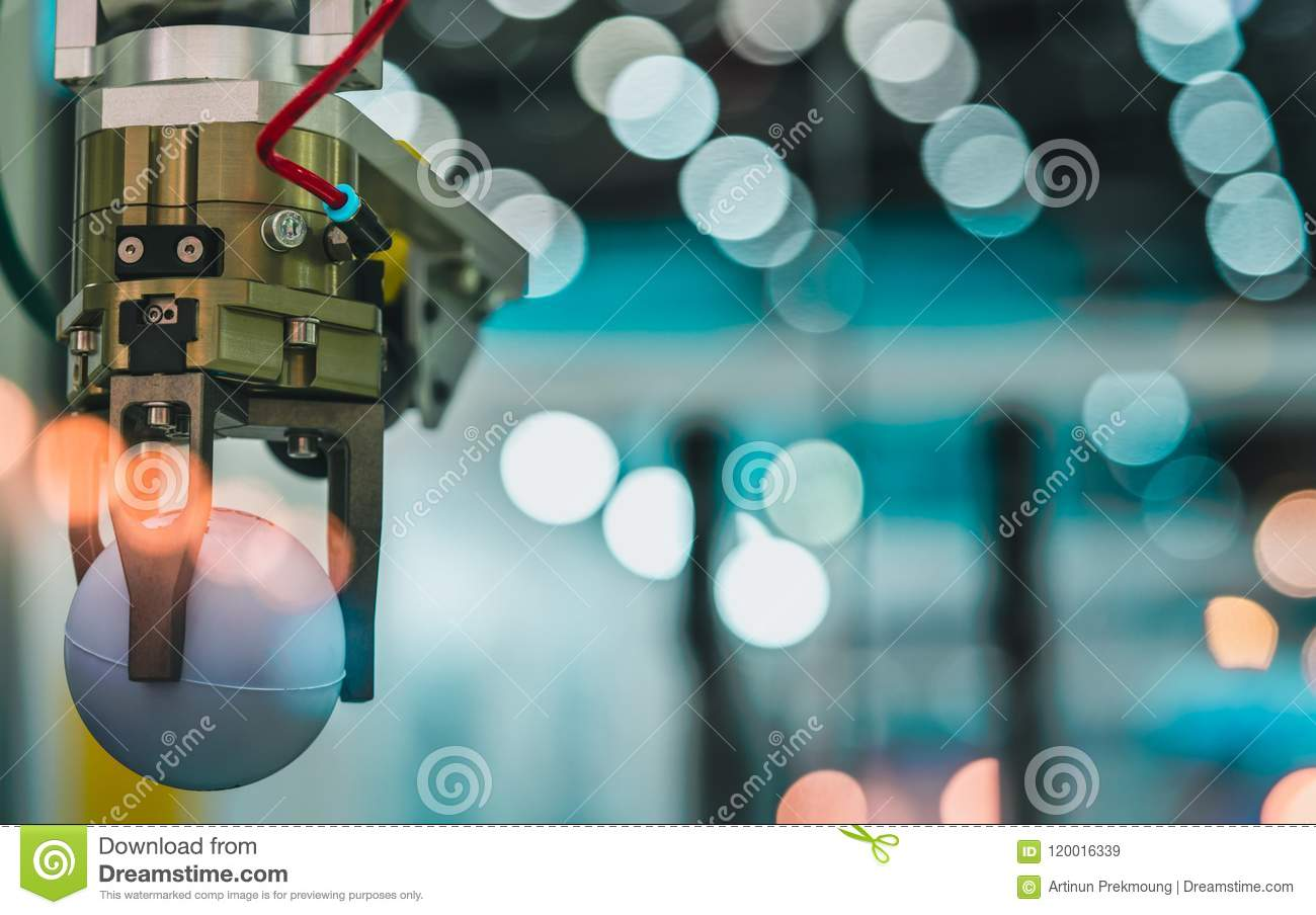 Closeup robot hand machine picking up white ball on bokeh blurred background. Use smart robot in manufacturing industry. Robotic