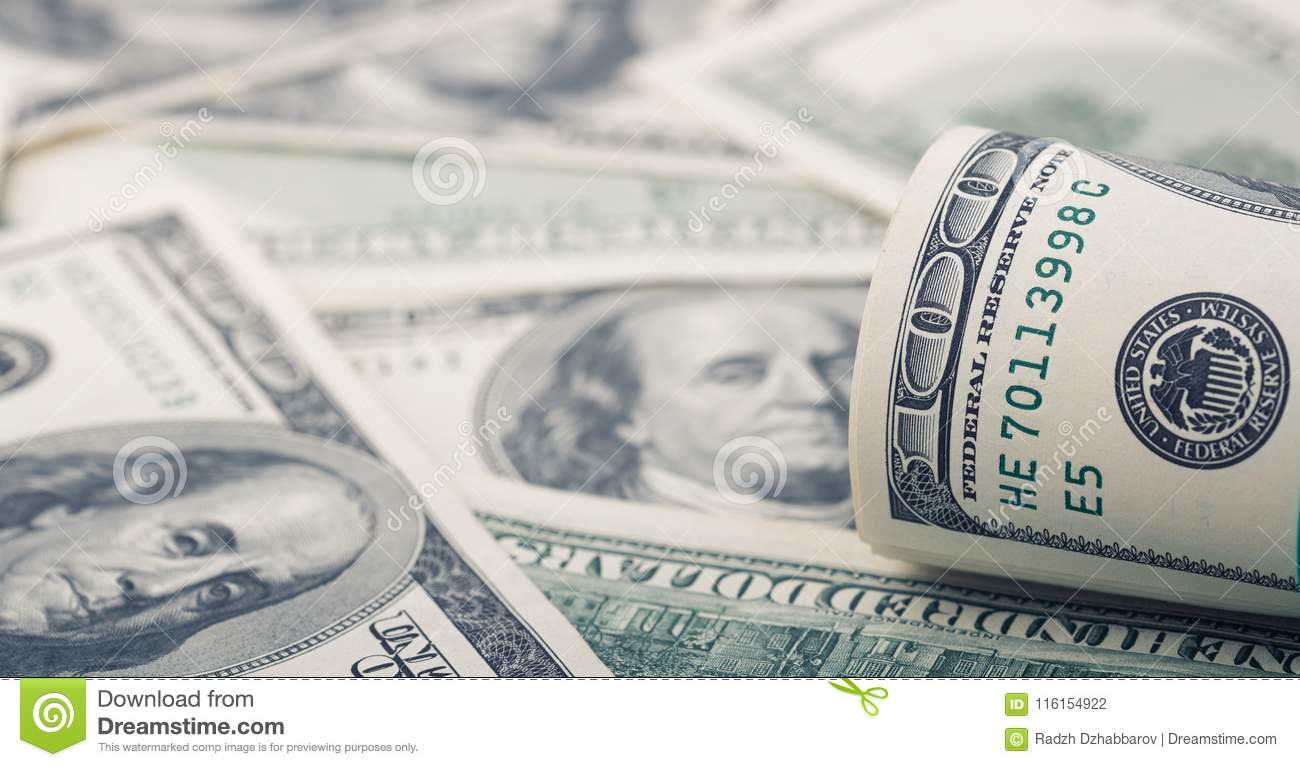 Closeup rolled dollar hundred on background American money dollar bill. Many US 100 banknote