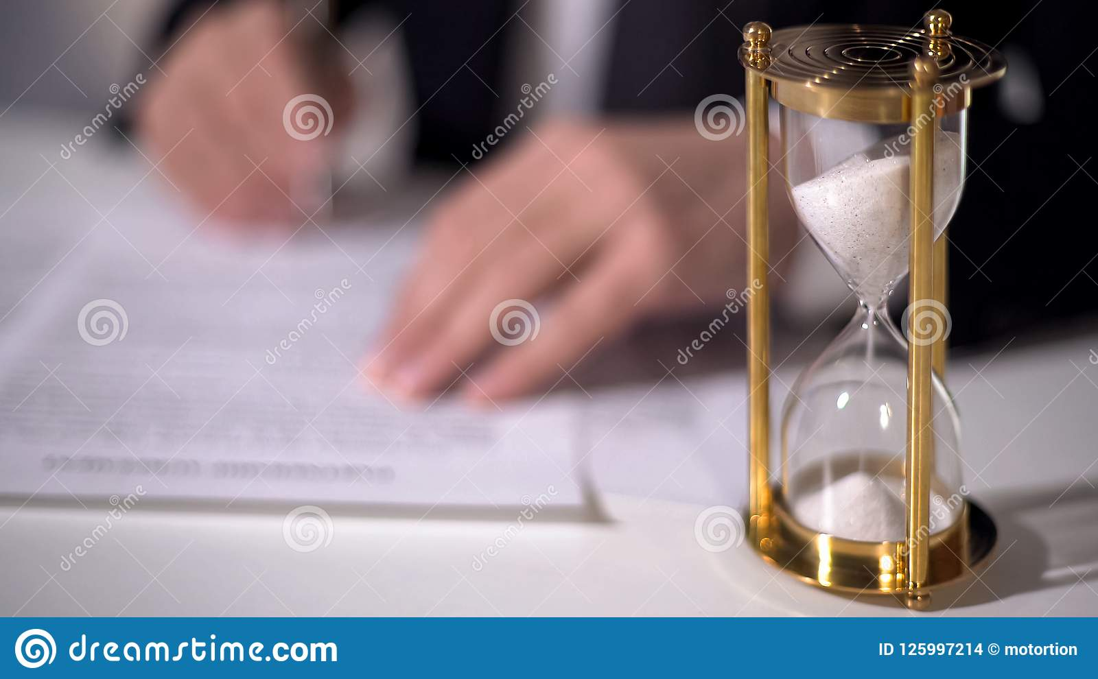 Closeup of sand clock measuring time, official signing important reform document