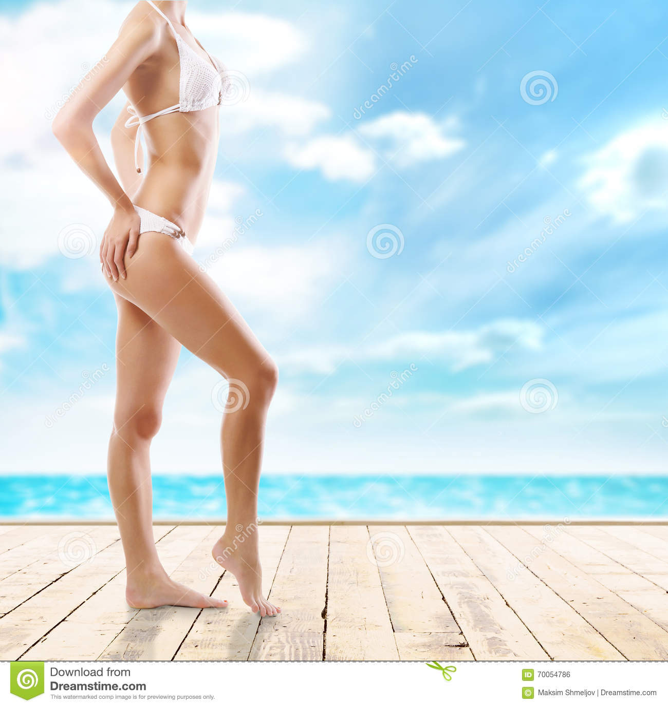 435e131034 Closeup of and sporty female body. Girl with a perfect body shape resting on  a summer vocation. Sea