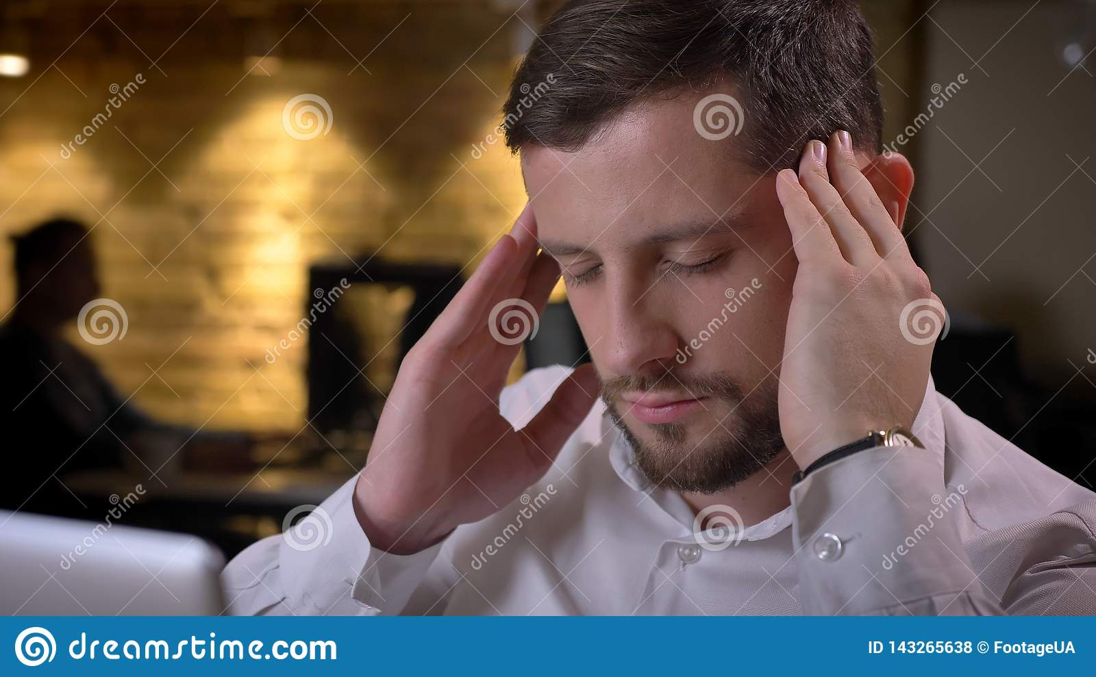 Closeup shoot of adult caucasian male employee having a headache and beind stressed and devastated indoors in the office