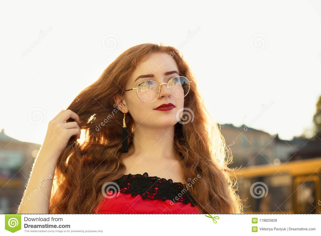 Closeup shot of lovely red haired woman with curly hair posing in evening  soft sunlight. Empty space