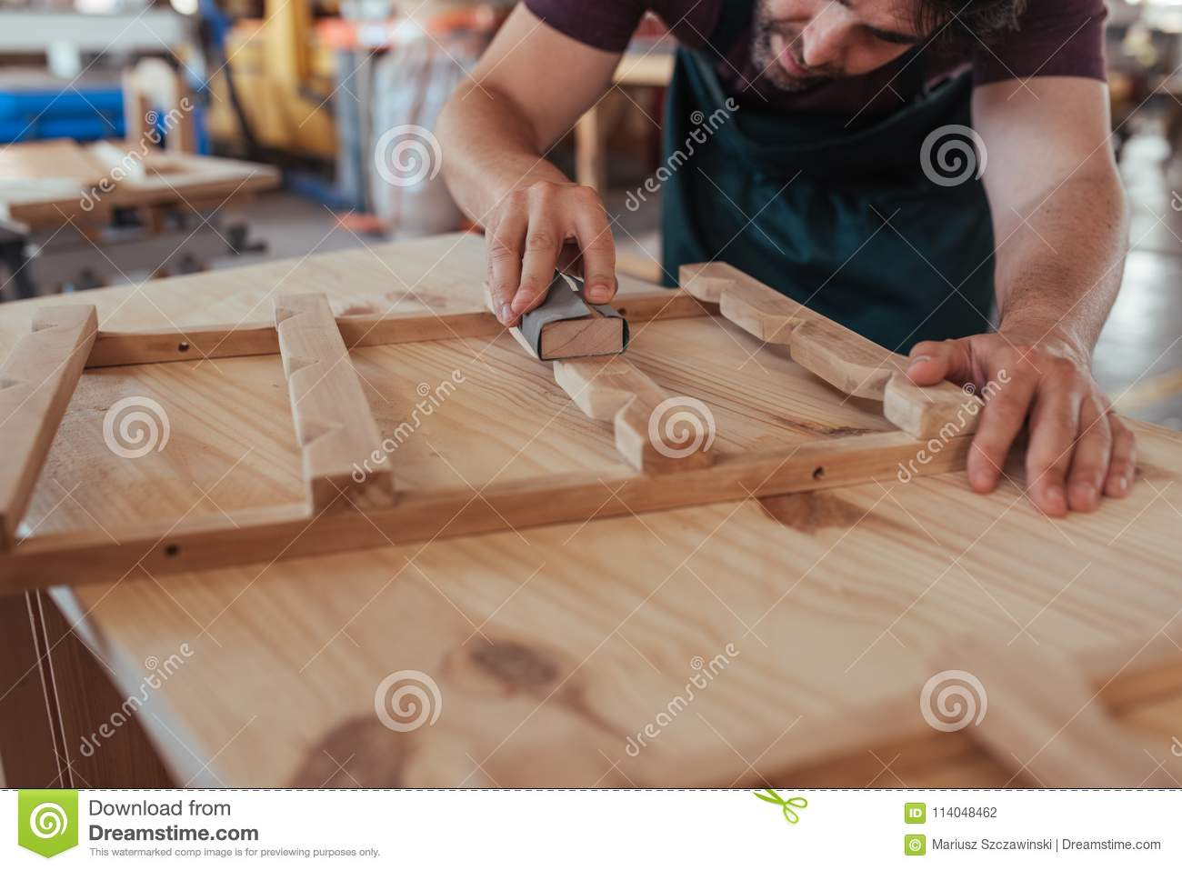 Craftsman Skillfully Sanding A Piece Of Wood In His Workshop Stock