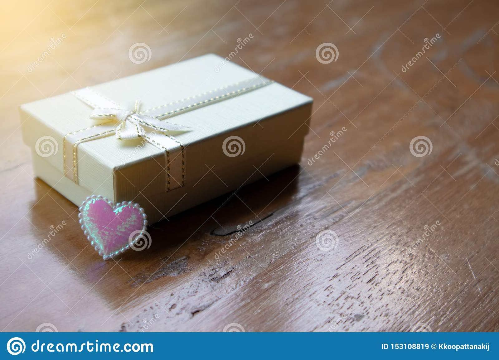 Closeup small white peatl gift box with white ribbon and the pink sparkle tiny heart