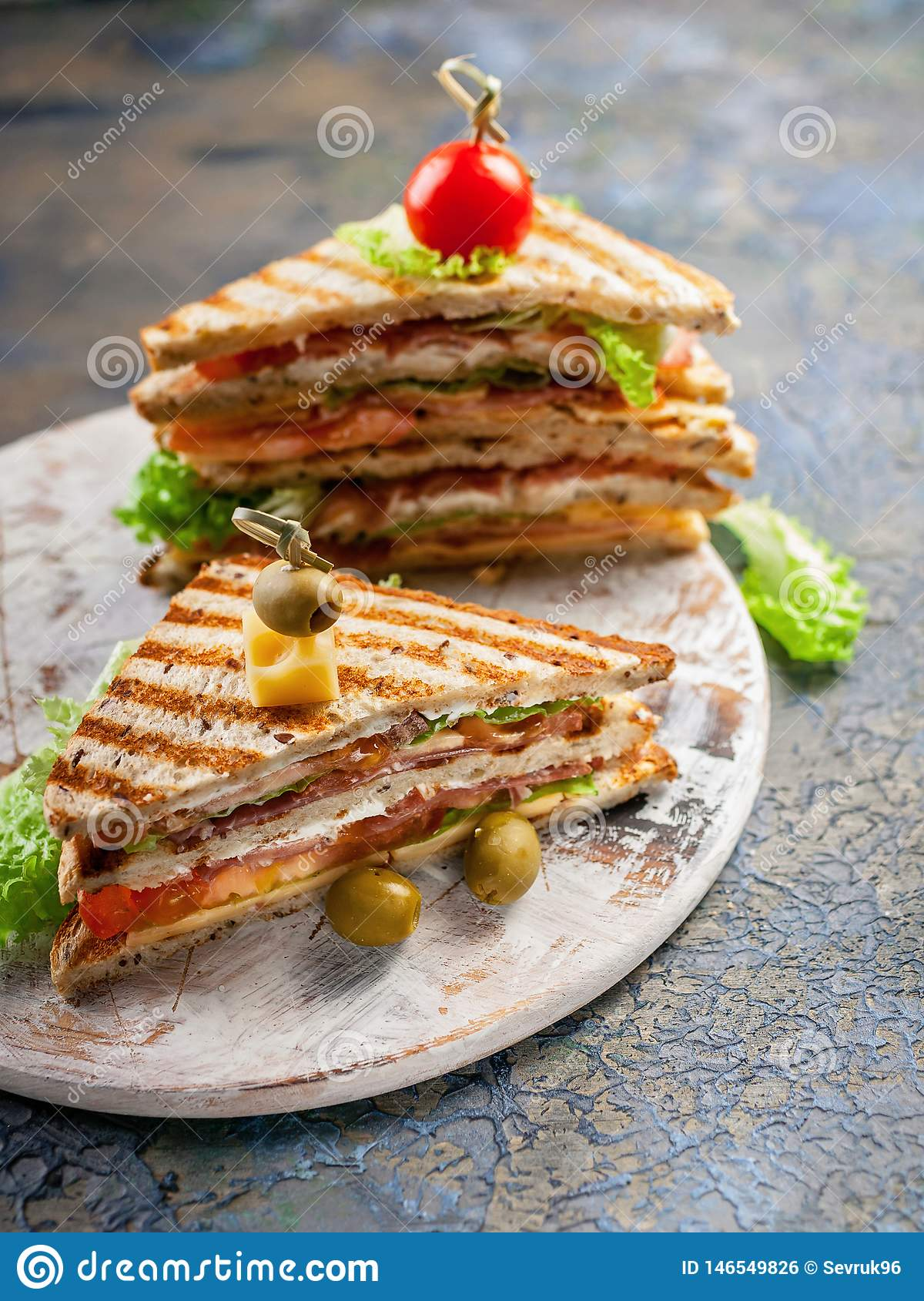 Closeup of a smoked beef sandwich and green salad on a round cutting board. Traditional breakfast or lunch. Vertical shot