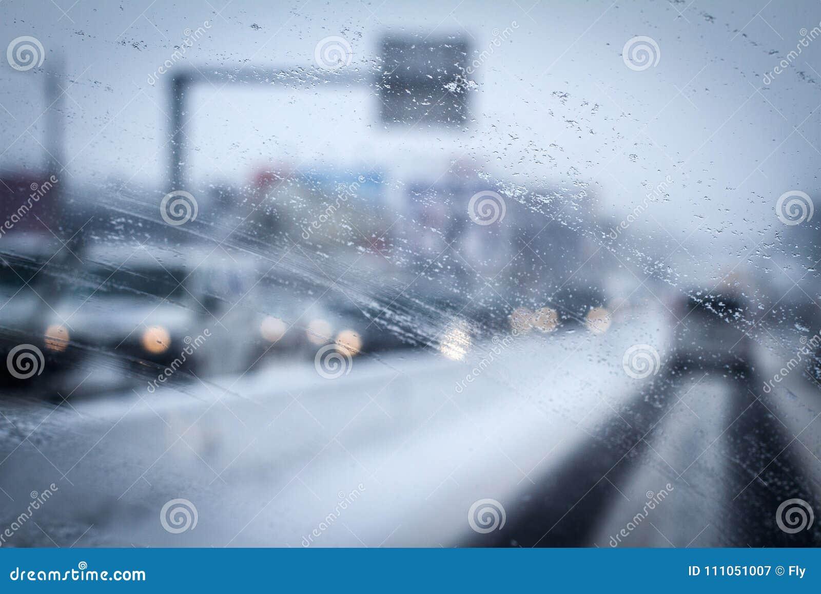 Closeup of rain drops drizzle on car windshield