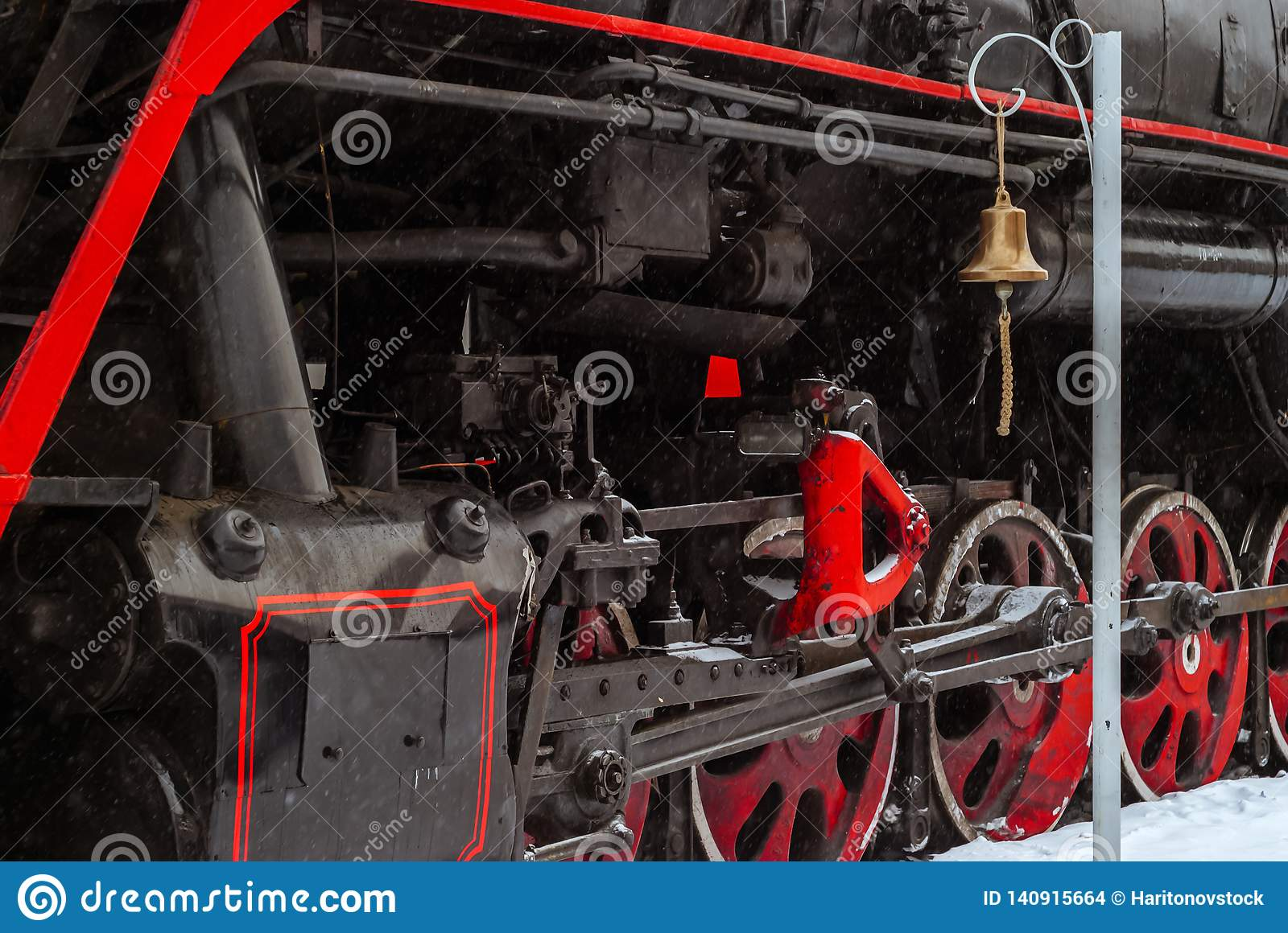 Closeup of a steam locomotive wheels with station bell
