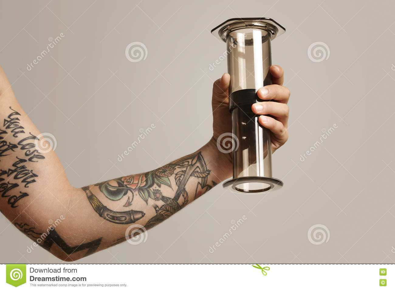 23ef251fb Clear light gray aeropress with reflections held by a tattooed young man, close  up shot