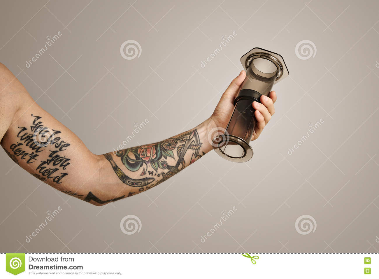 0479b1c3b A close up shot of a tattooed arm and hand holding a light gray aeropress  nontraditional coffee brewing equipment