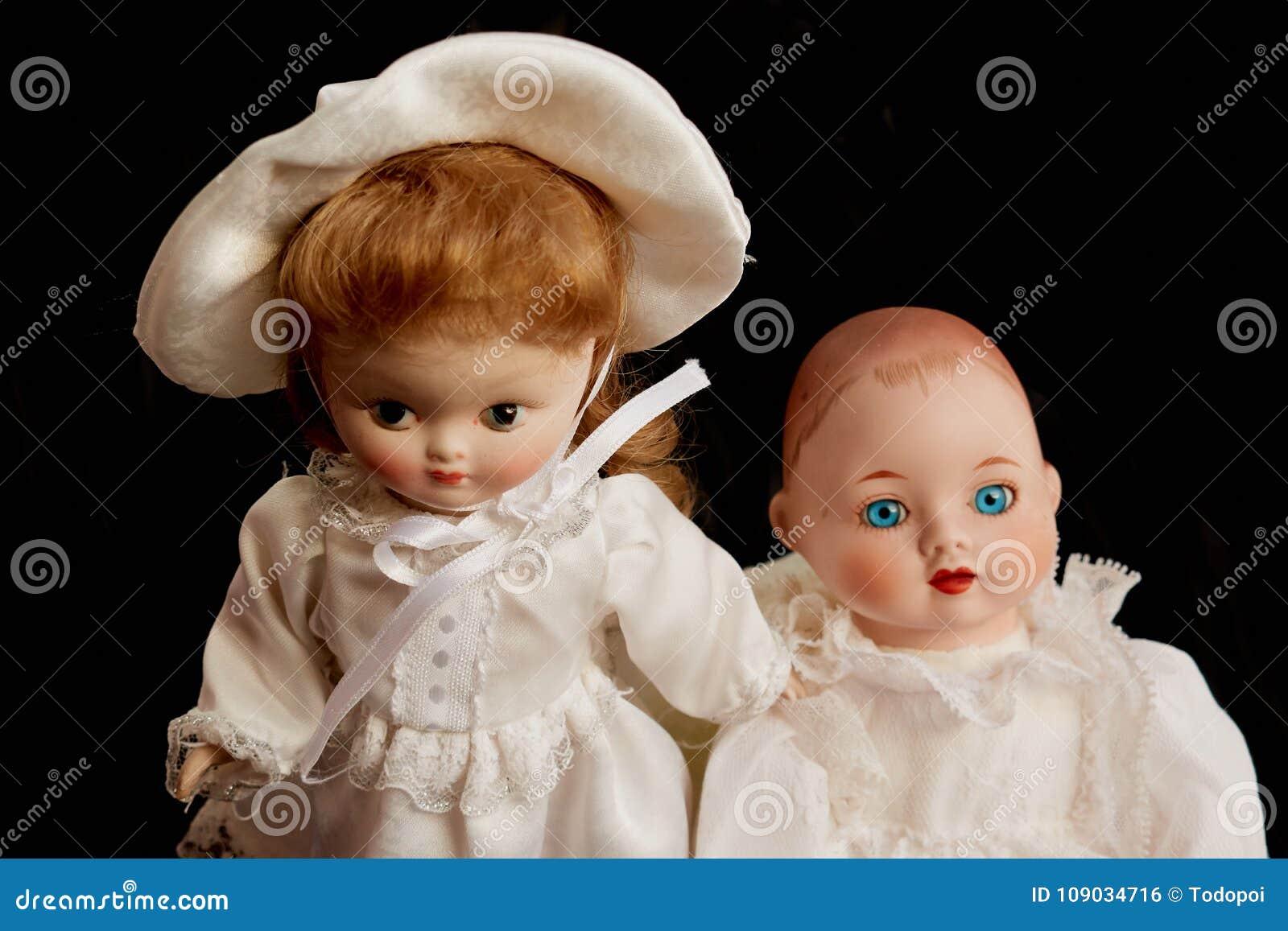 Closeup of two old porcelain dolls on black background
