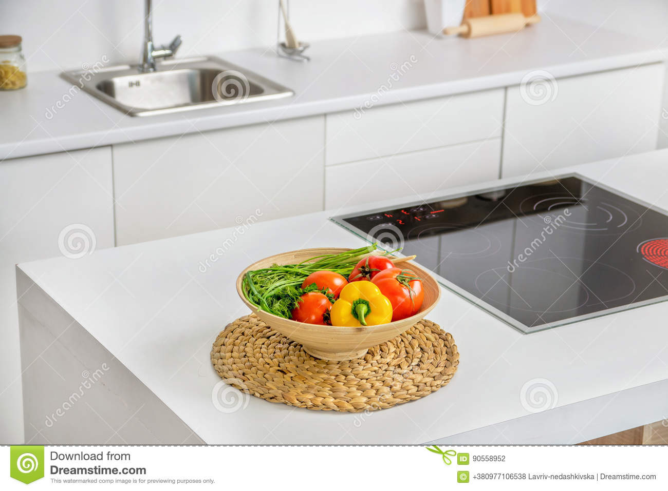 Closeup of vegetables in the bowl in modern white kitchen with induction cooking heater and sink on background