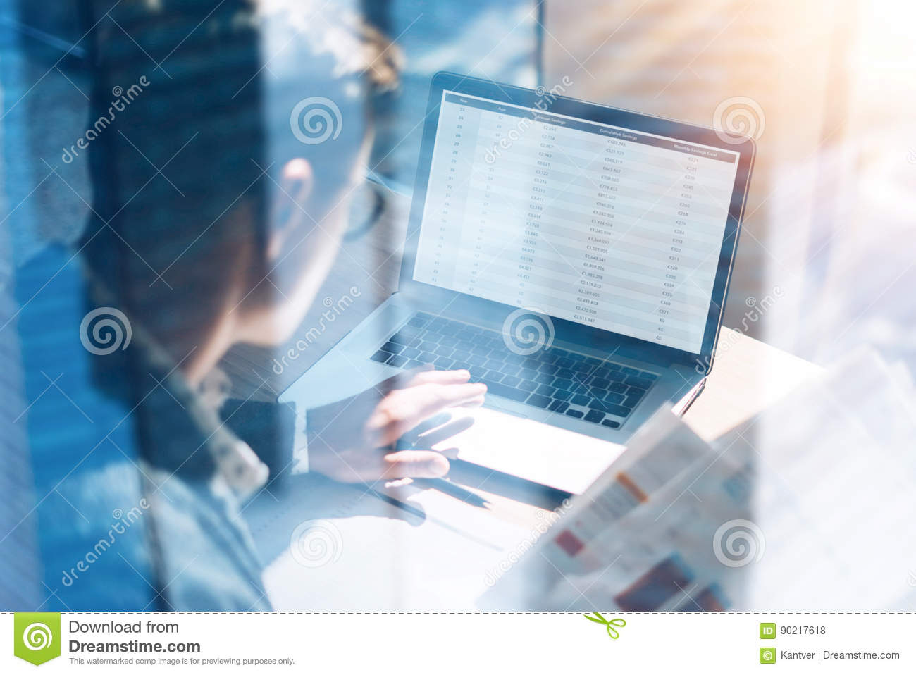 Closeup view of banking finance analyst in eyeglasses working at sunny office on laptop while sitting at wooden table
