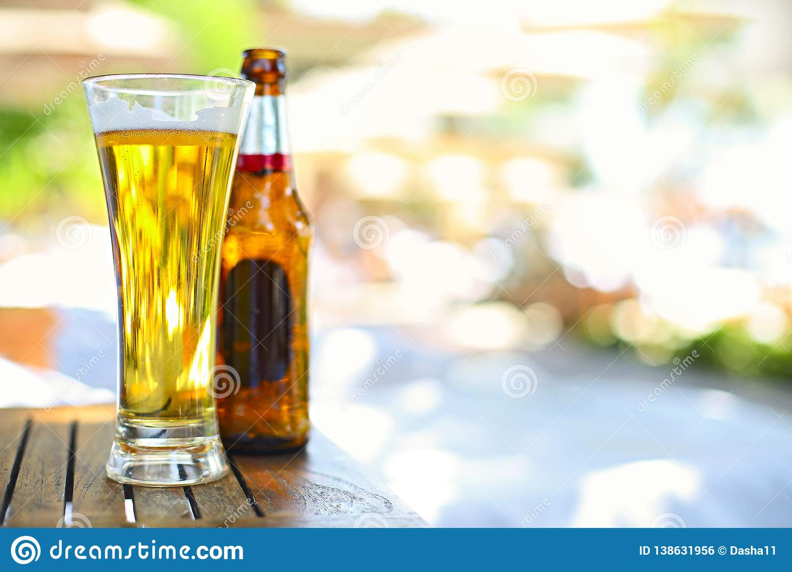 Closeup view of beer bottle and the glass in the garden