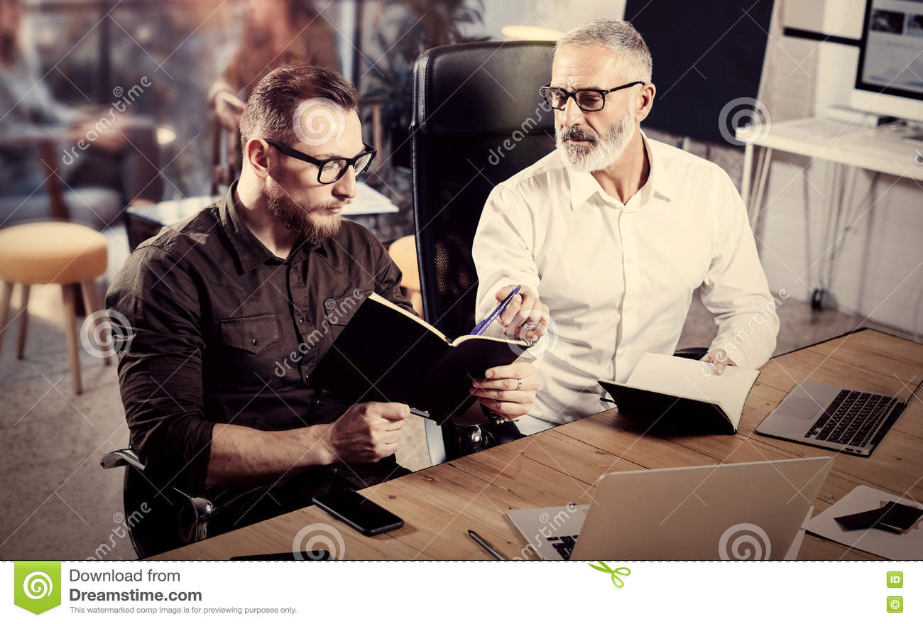 Closeup view of business people brainstorming process.Bearded adult man making notes in notebook.Coworkers teamwork in
