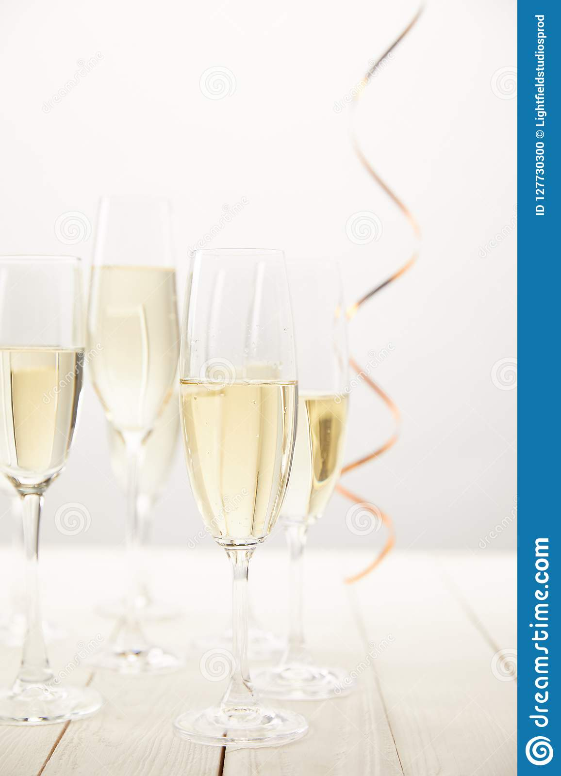 closeup view of champagne glasses with ribbon on white wooden table, holiday concept