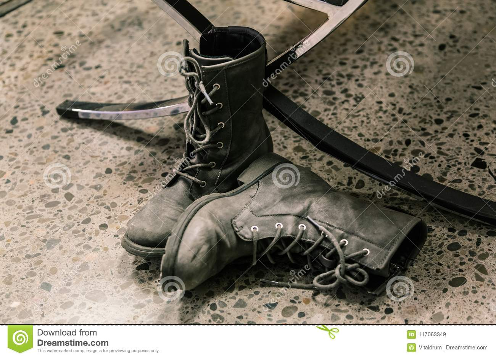 closeup view of dark grey pair of stylish boots, man`s wear on dark concrete floor
