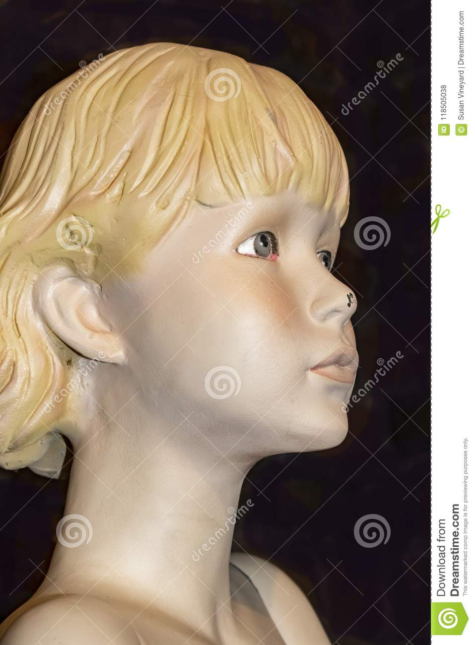 Closeup view of face of old retro mannequin girl with short blond hair and a chip in her nose and a spider behind her ear against