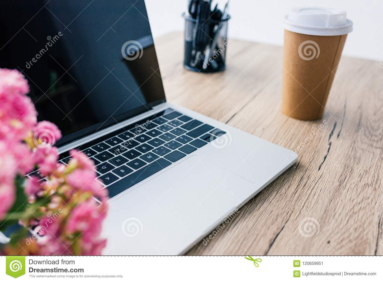closeup view of laptop with blank screen, flowers, paper cup of coffee and stationery