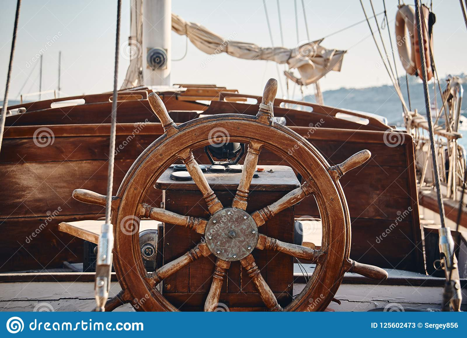 Closeup Of A Vintage Hand Wheel On A Wooden Sailing Yacht Stock