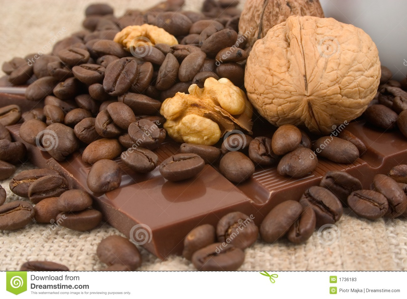 Closeup of cup of coffee, walnuts, coffee beans and bar of chocolate ...