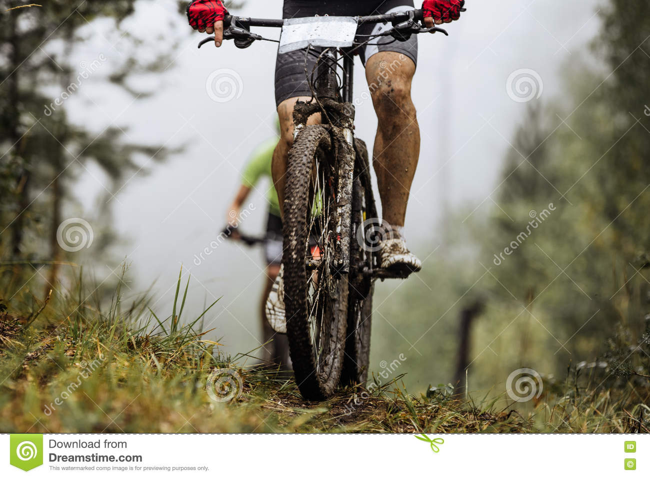 Closeup wheel mountainbike and feet rider in spray of dirt