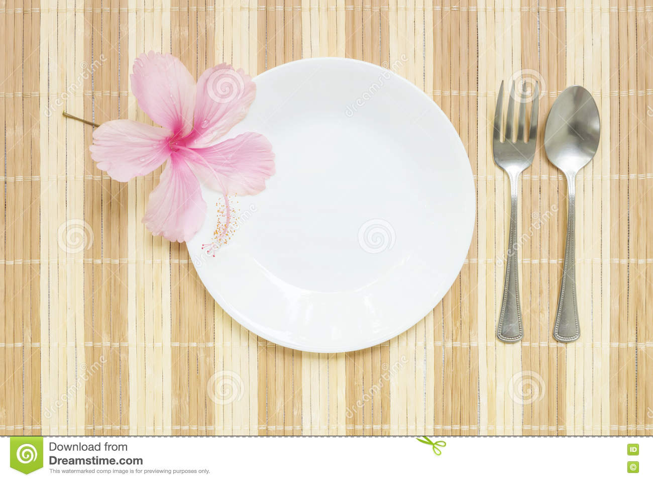 Dinner table background - Closeup White Ceramic Dish With Stainless Fork And Spoon With Pink Flower On Wood Mat Textured