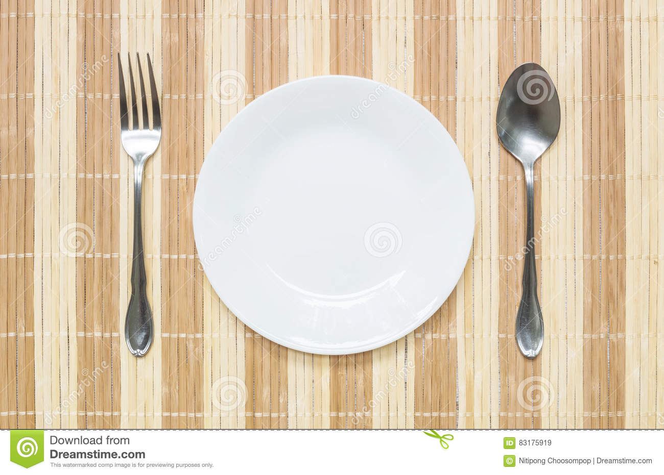 Kitchen table top view - Closeup White Ceramic Dish With Stainless Fork And Spoon On Wood Mat Textured Background On Dining