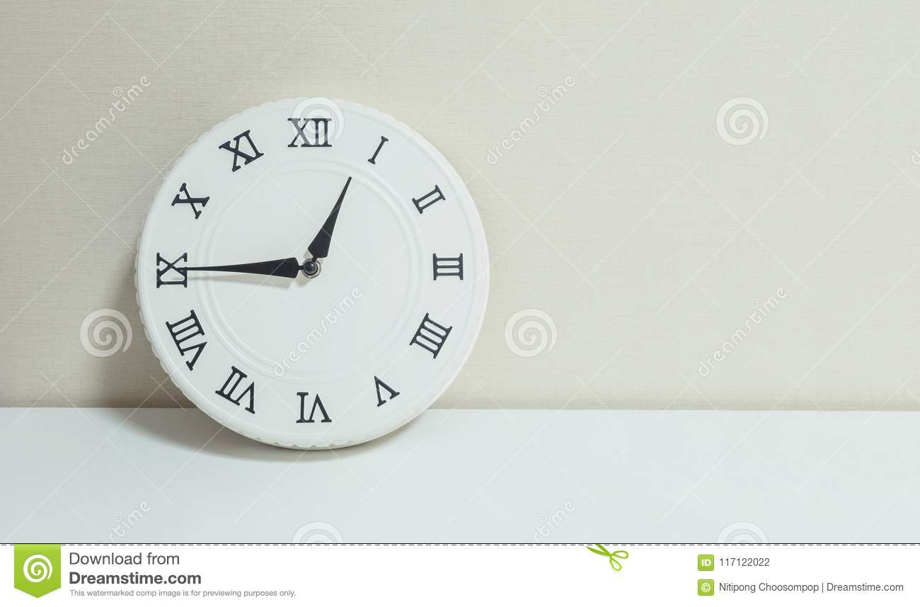 Closeup white clock for decorate show a quarter to one p.m. or 12:45 p.m. on white wood desk and cream wallpaper textured backgrou