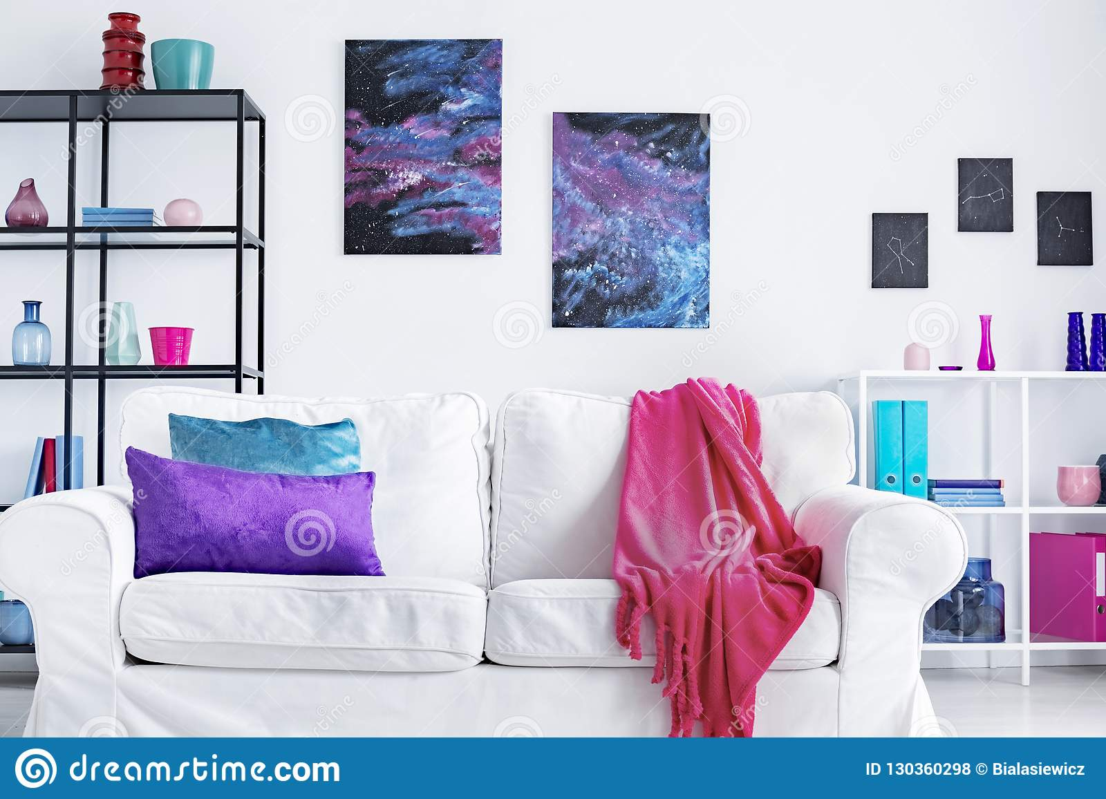 Closeup of white comfortable couch with pink blanket and purple and blue pillows in modern living room interior, real photo