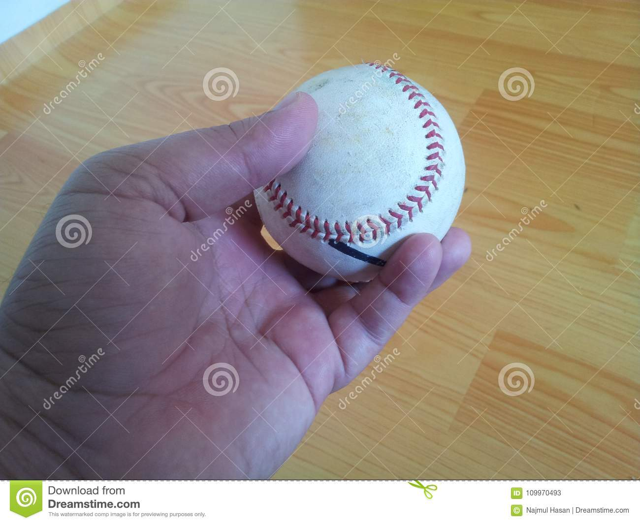 Closeup and of a white cricket hard ball in hands