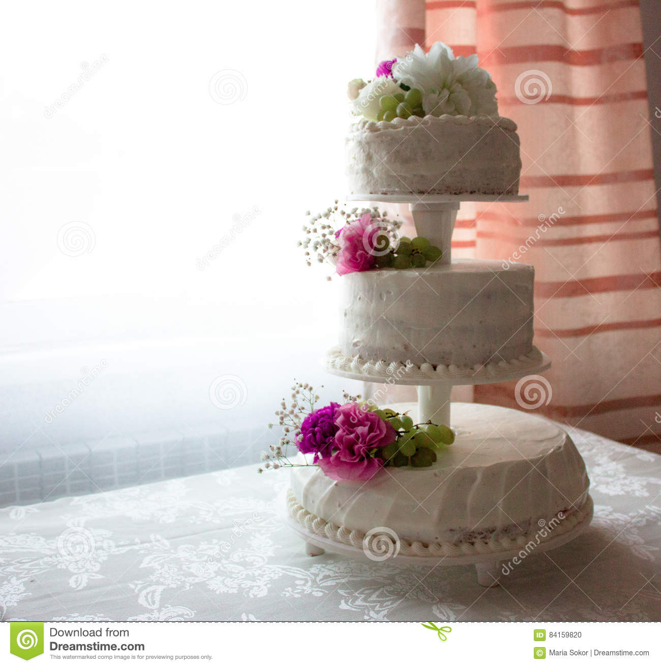 Closeup Of White Wedding Cake With Brown Ribbon And Flowers On Top ...