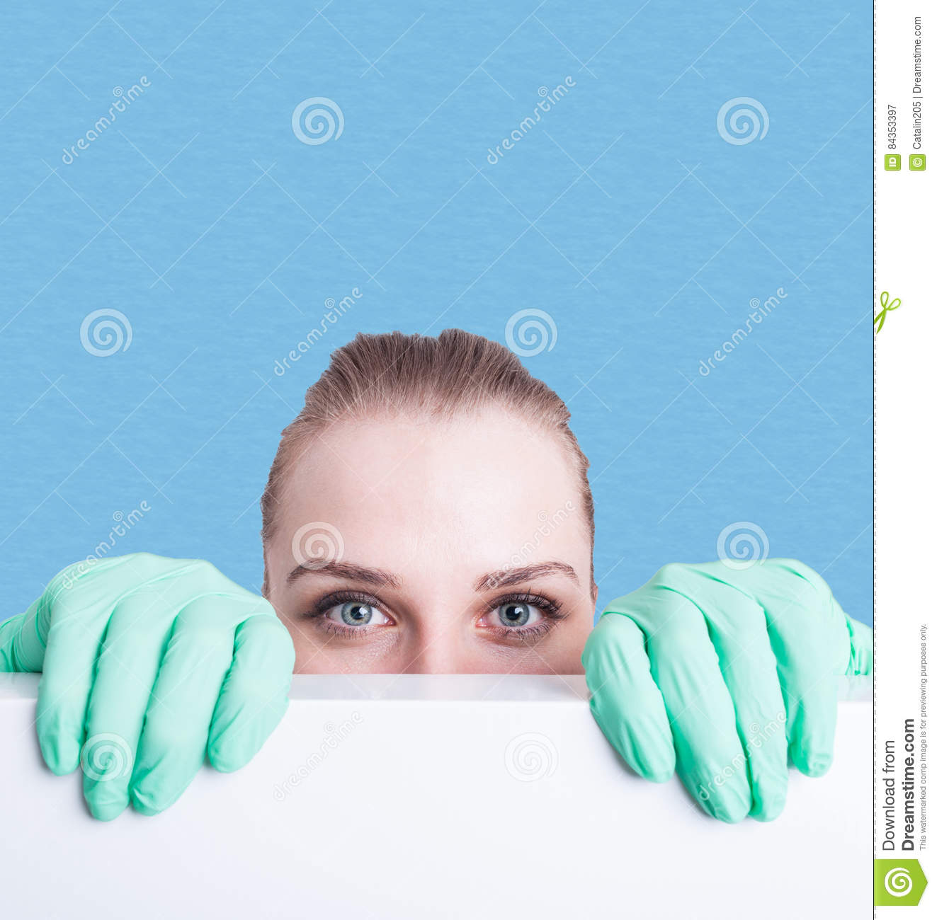 Closeup of woman medic hiding behind blank poster