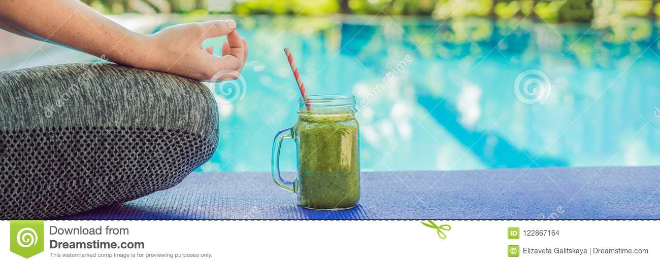 Closeup of a woman`s hands during meditation with a green smoothies of spinach, orange and banana on the background of the pool B