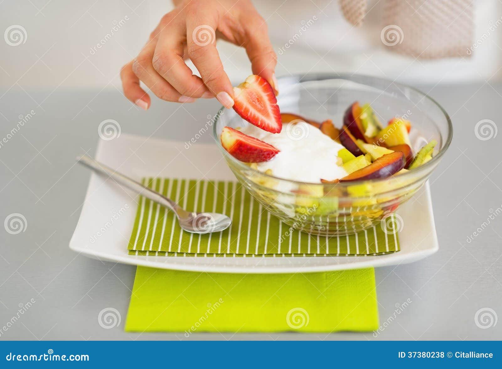 Closeup on woman serving fresh fruit salad