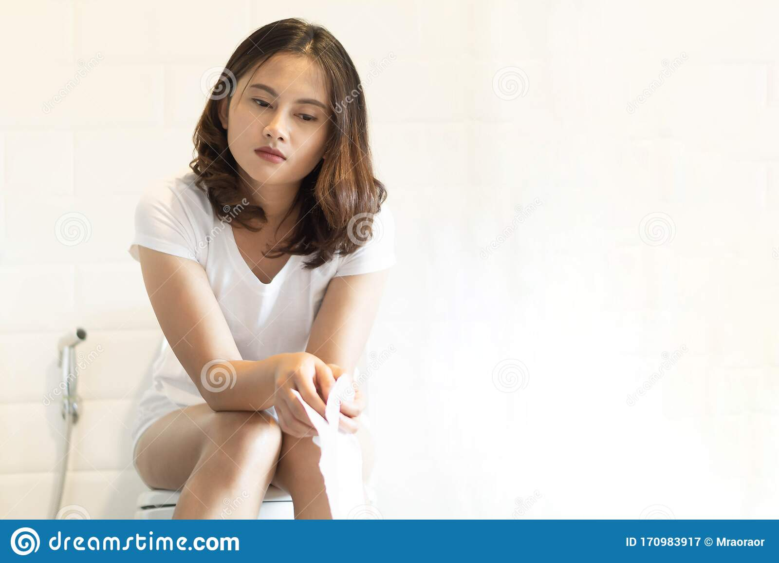 Closeup Woman Sitting On Toilet In The Morning With Foot