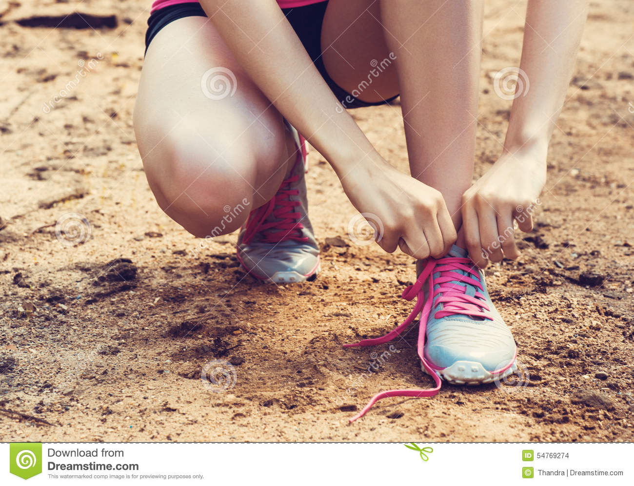 Closeup of woman tying shoe laces. Female sport fitness runner getting ready for jogging outdoors on forest path i