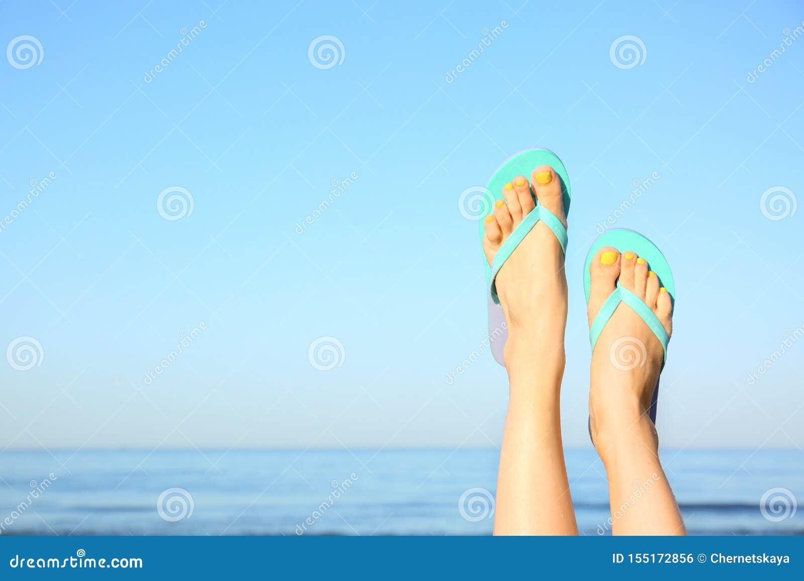 Closeup of woman wearing flip flops near sea, space text. Beach accessories