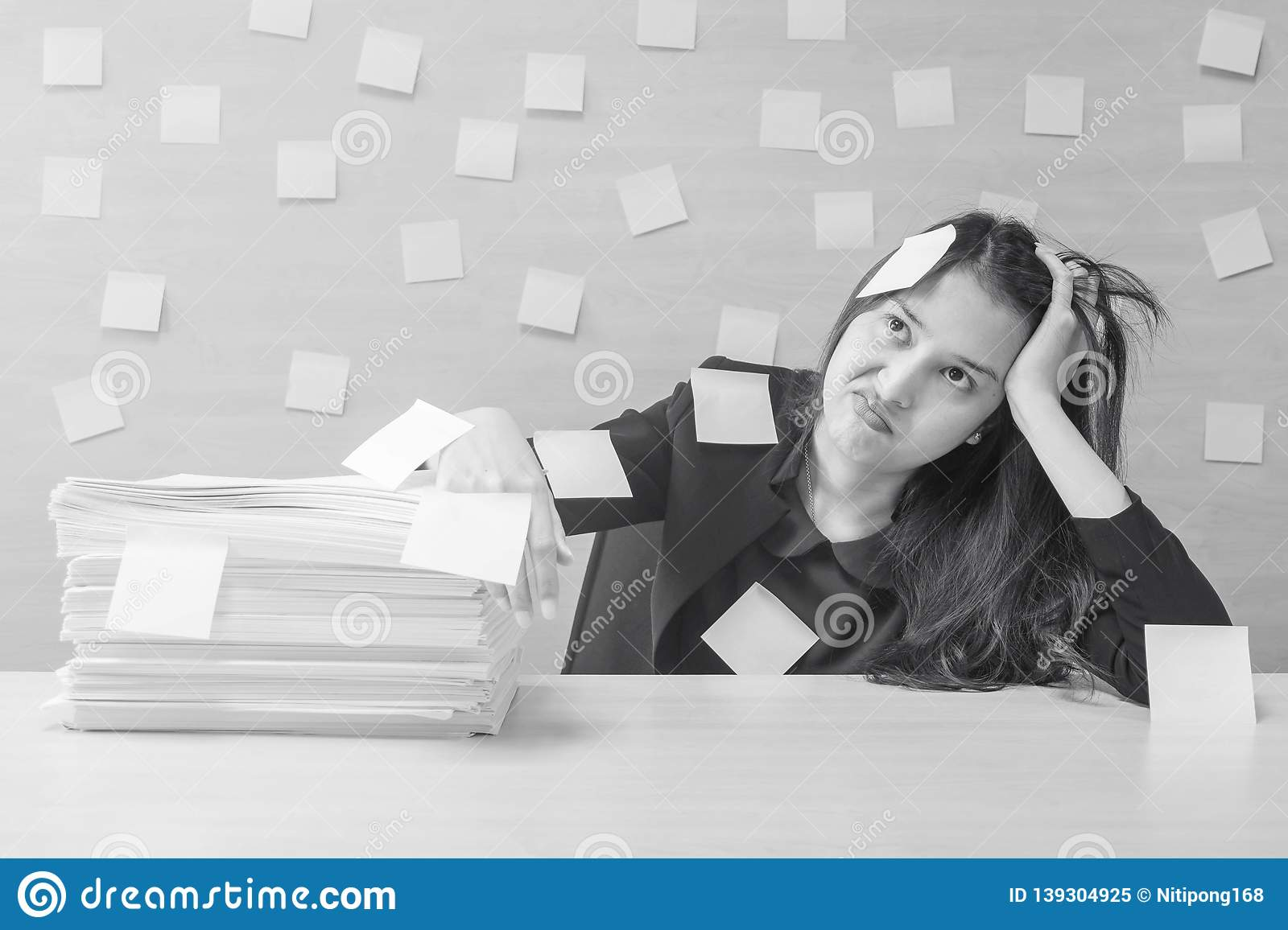 Closeup working woman are boring from hard work and pile of work paper in front of her in work concept on blurred wooden desk and