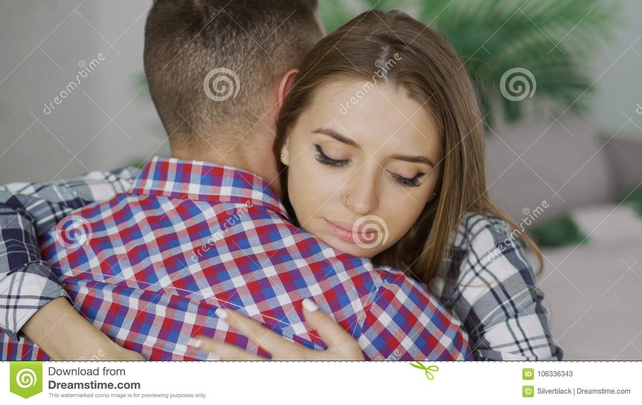 Closeup of young upset couple embrace each other after quarrel. Woman looking wistful and sad hug her boyfrined at home