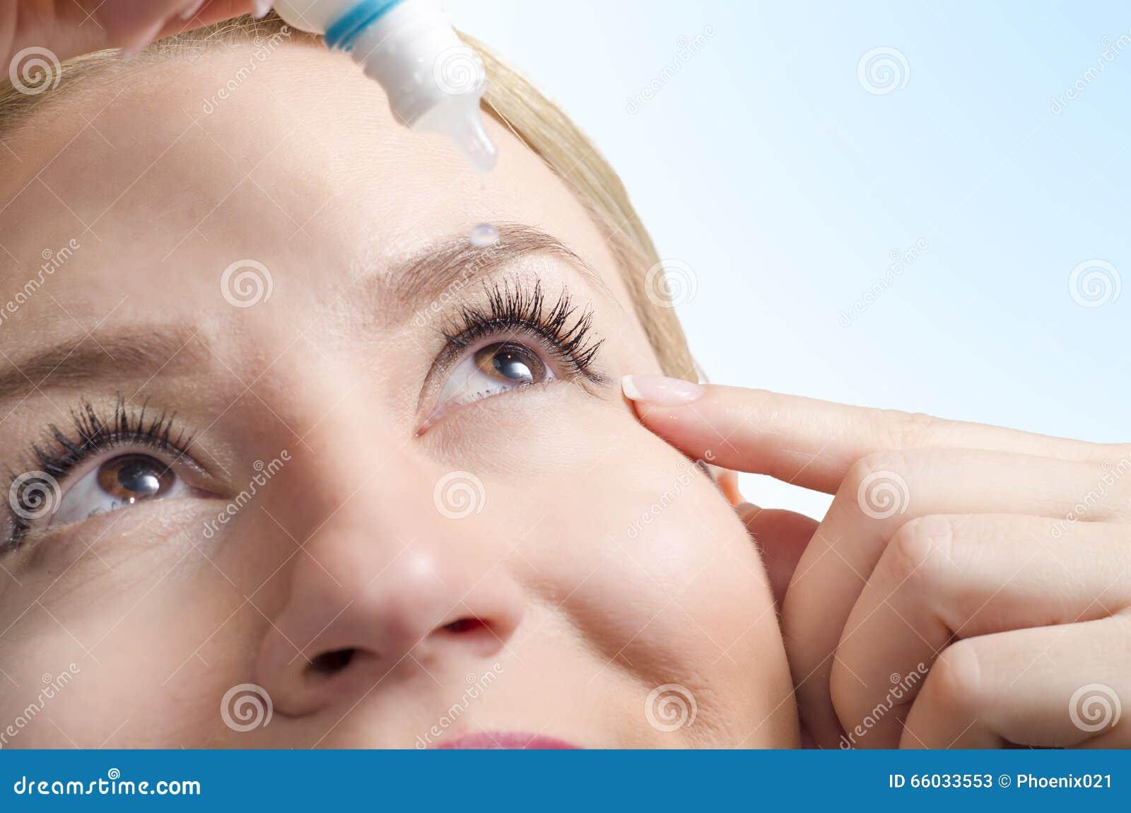 Closeup of young woman applying eye drops